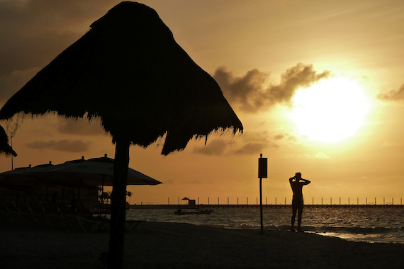 image of a man on the beach enjoying the sunrise in Playa Del Carmen, Mexico, at the Fusion Hotel