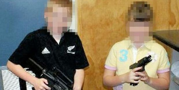UK cop's shocking Kiwi holiday Facebook photo – children  in New Zealand holding an assault rifle and a Glock pistol.