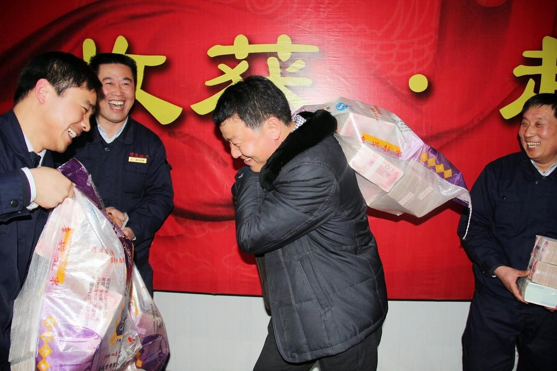 SEORANG pekerja memikul guni yang mengandungi wang tunai pada satu majlis penyerahan bonus oleh majikannya di Zhecheng baru-baru ini.