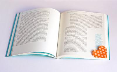 Corazón de papel marcando esquina de una hoja de un libro