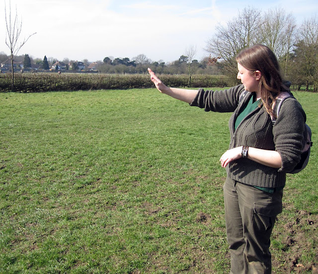 Jenny Price of BCS gesturing towards a pleached hedge across the meadow in Jubilee Country Park