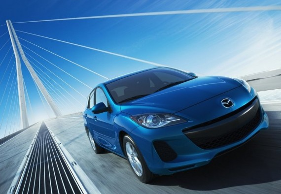 Front 3/4 view of blue Mazda 3 crossing bridge