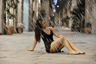 hot girl sitting on ground in heavy rain