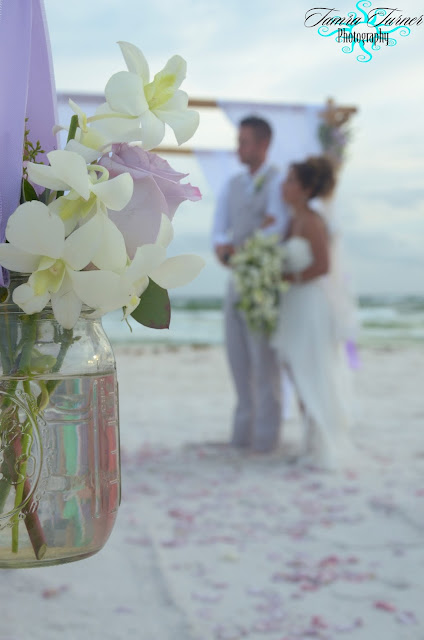 vases of fresh flowers line the aisle for this Panama City Beach wedding