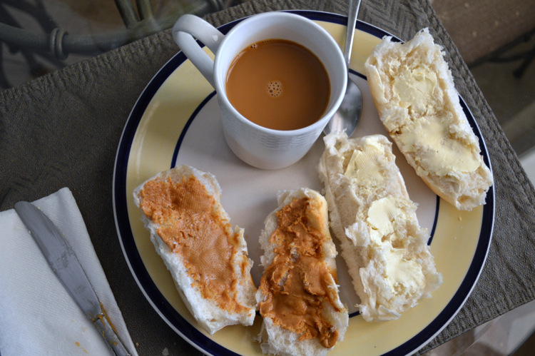 a breakfast of cuban bread spread with peanut butter and butter with a side of cafe con leche also known as cafe au lait