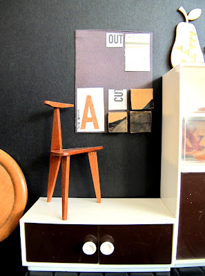 Modern dolls' house miniature collage art work hanging on a black wall. In front of it is an art chair. On the left is a cabinet  with a wooden pear on top of it.