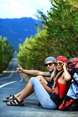 foto de una pareja sentada al lada de la carretera haciendo autoestop