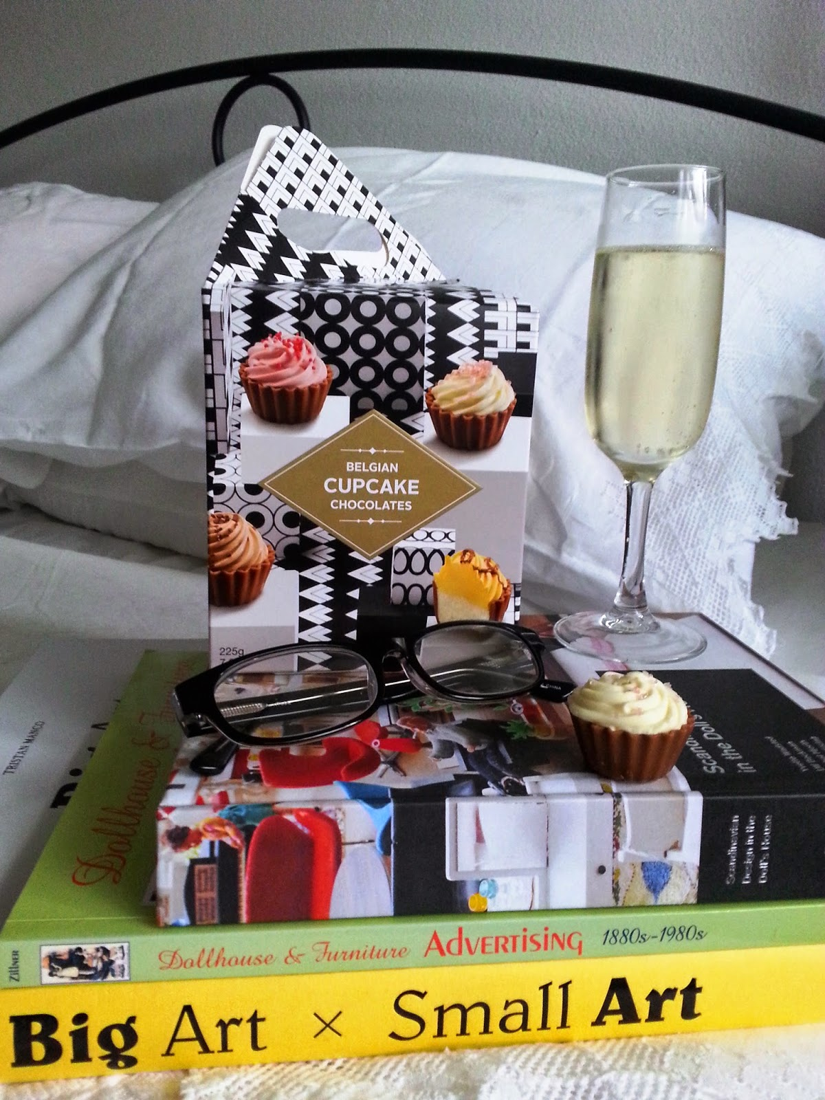 Pile of three books on a bed, with a box of miniature cupcake-shaped chocolates, a pair of reading glasses and a glass of sparkling wine on top.