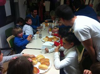 En la imagen se pueden ver a todos los niños comiendo bocatas y bebiendo refrescos.
