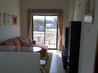image of tv room situated upstairs with a sliding door leading out to balcony