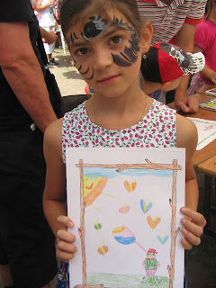 Óvódás arcfestett kislány néz szembe. A kezében tartja rajzát, amin Törpmanó kirándul témát dolgozza fel. A lap felső sarkában vidám napocska kukucskál ki a felhők közül, Törpmanó körül meg sok a szivárvány-színű lepke.