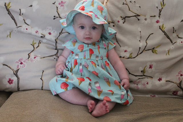 baby girl wearing aqua blue dress with ice cream and lollipop pattern and matching hat
