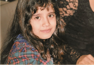Photograph shows a girl with long dark hair, her back to the left side of the picture. She wears a green and red plaid shirt. She has a hesitant expression.