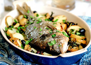 Whole roast bream with potatoes and olives. Whole bream roast on a bed of potatoes and olives.