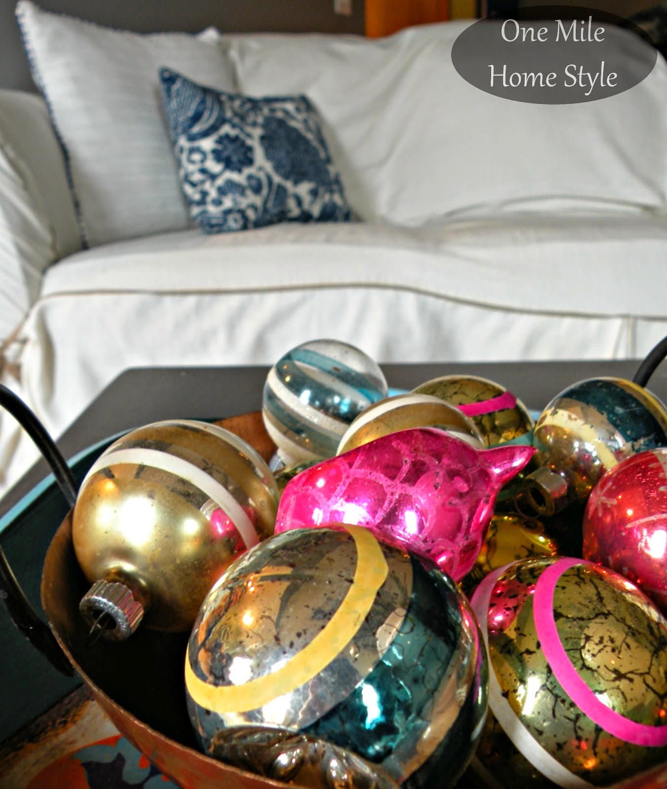 Copper bowl filled with colorful vintage Christmas ornaments