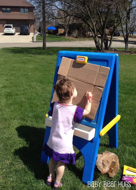 girl drawing outdoors on a fisher price easel
