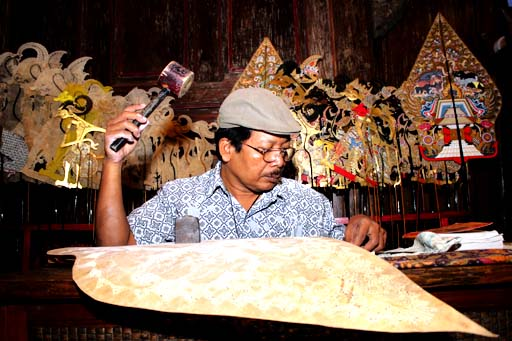 Hand made: An artisan uses a wooden hammer to make wayang kulit
