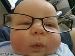 Close up photograph of a baby&#039;s face with eyeglasses.