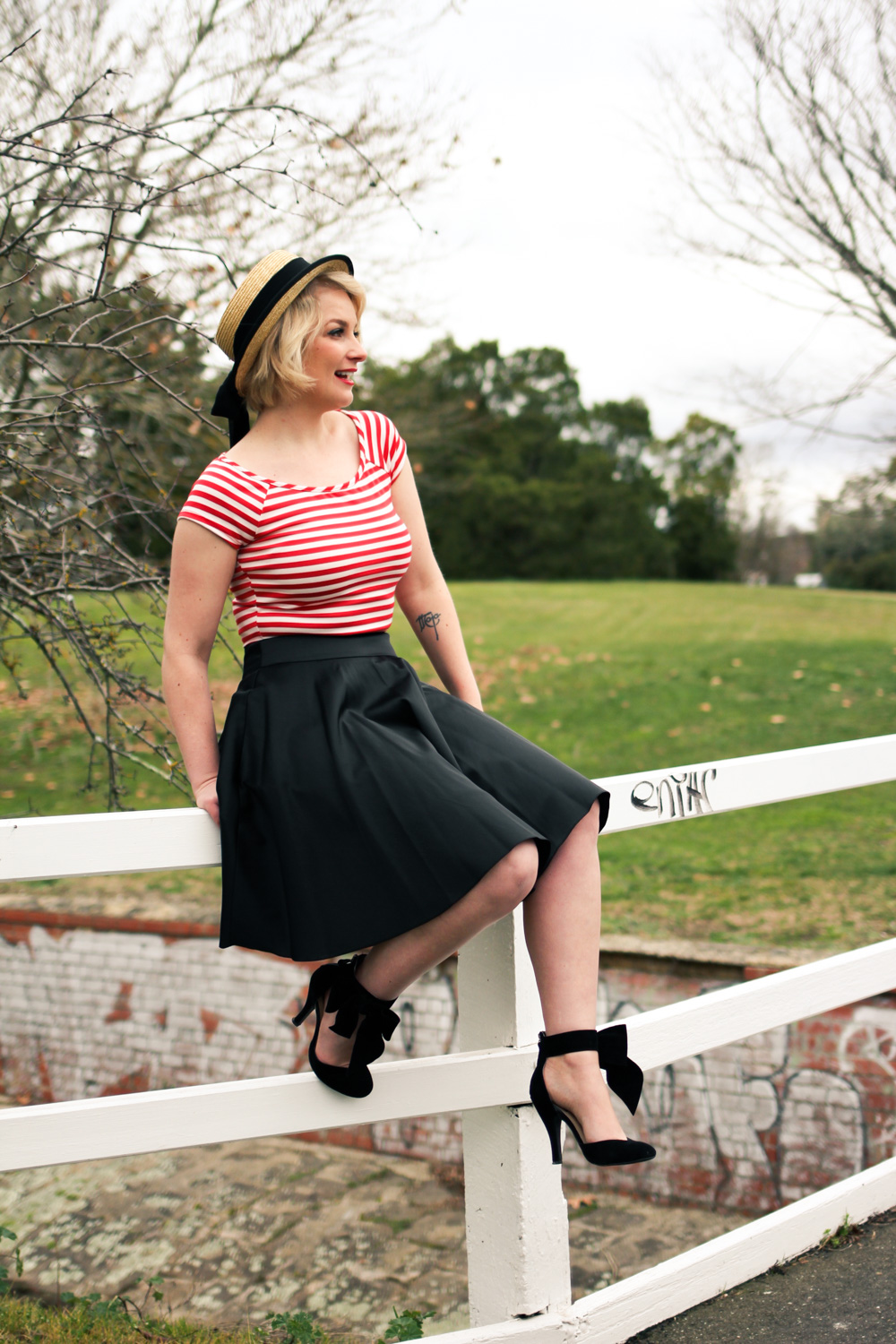 @findingfemme in red striped crop top, black Review Australia skirt and Modcloth bow heels with straw boater.