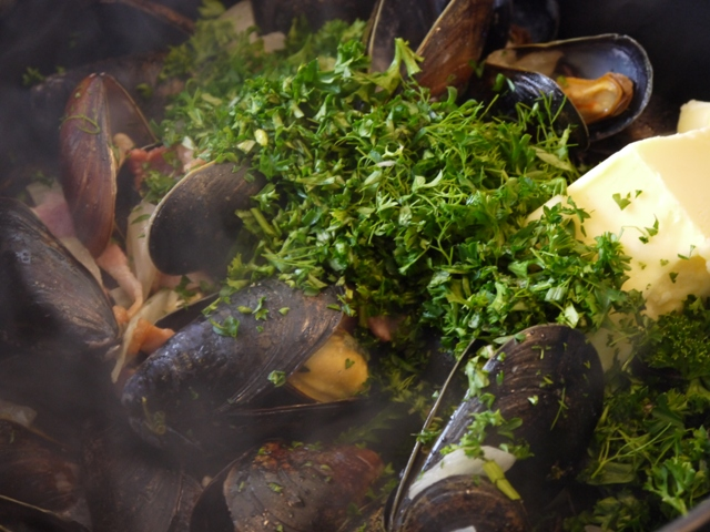 Once the mussels have opened, add the parsley, butter and lemon juice ...
