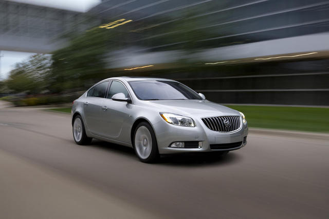 Front three-quarters view of silver 2012 Buick Regal E-Assist driving on city street