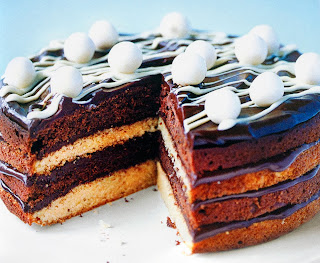 Sponge cake with alternating white and brown layers sandwiched with ganache topped with chocolate ganache and a white chocolate ribbon and white chocolate balls
