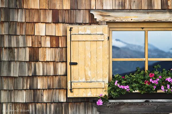 Hüttenfenster mit Blumen Südtirol Spiegelbild Berge mit Schnee