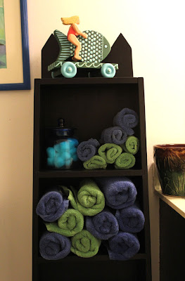 painted blacked shelving unit with towels and sculpture