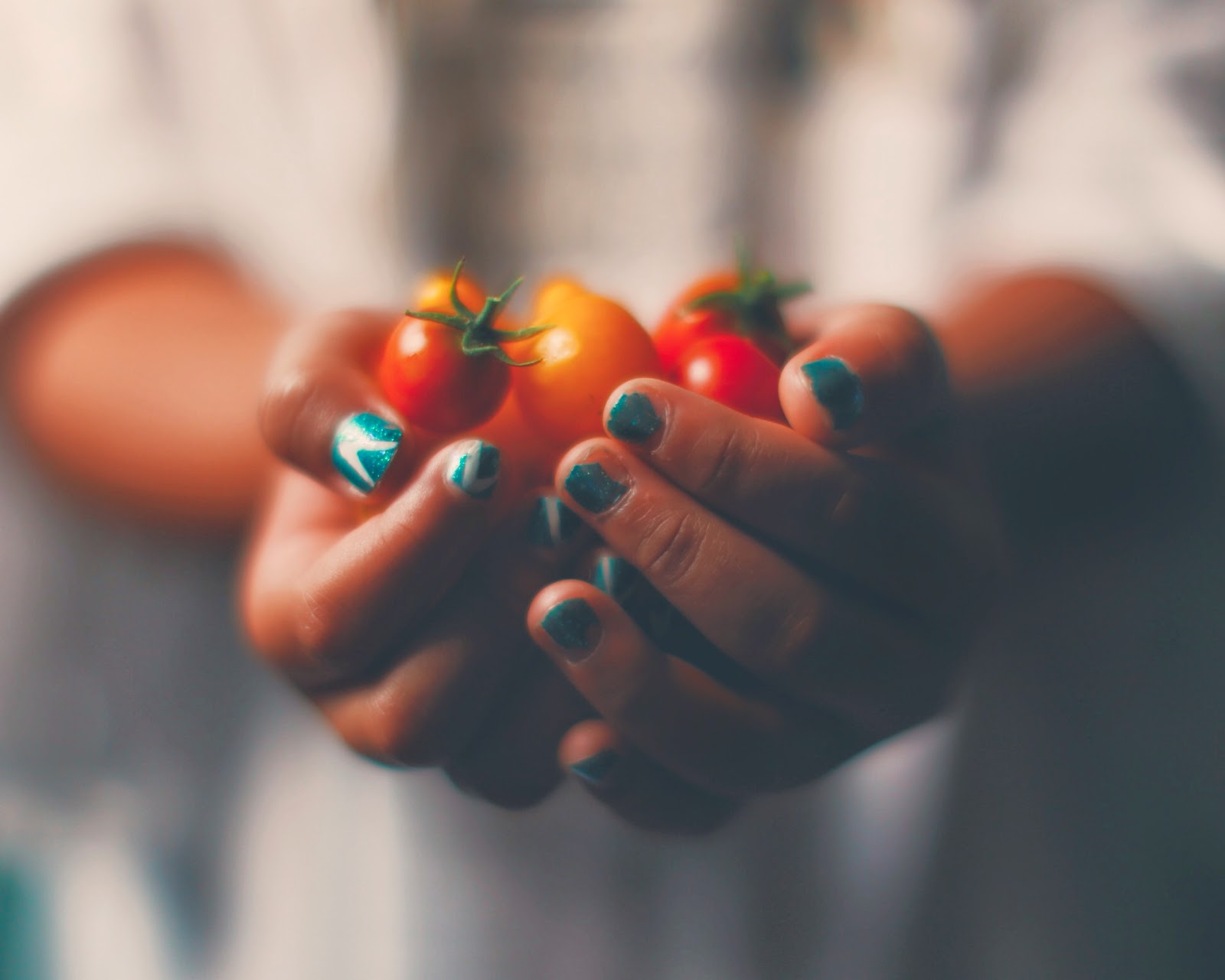 tomatoes in hands fingernails painted
