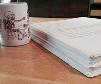 Picture Description: Stack of printed paper sits next to a coffee cup. The stack goes about half way, about an inch and a half, up the coffee cup. On the cup is a picture of a skeleton drinking coffee.