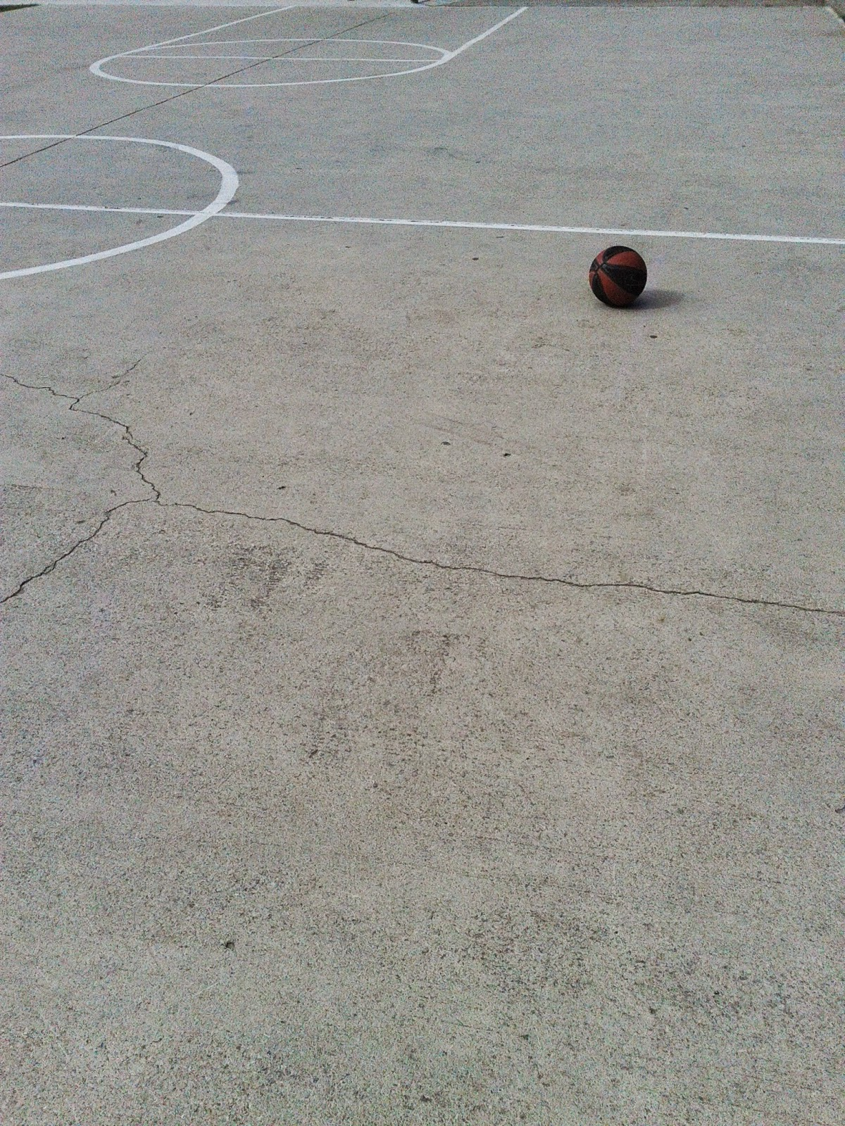 Lone basketball on an outdoor court