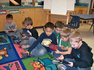 Children sitting on a rug at school playing educational games.