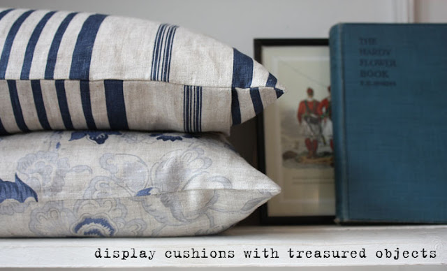 Two cushions on display with an antique book.