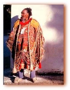 Foto do interno esquizofrênico Arthur Bispo do Rosário vestido com o seu Manto da Apresentação