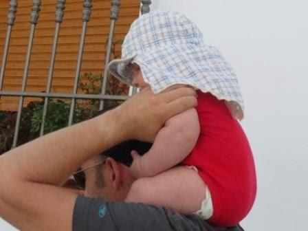 Baby das im Urlaub auf der Schulter getragen wird