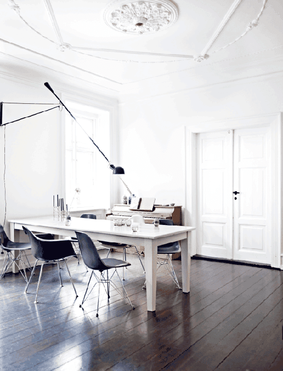 Dining room with dark floors, ceiling moldings and a Parisian loft attitude
