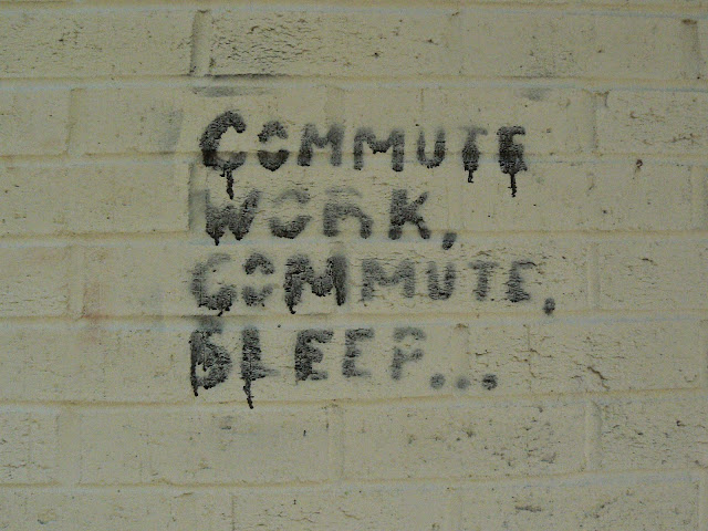 Graffiti on a wall reading Commute Work, Commute Sleep....