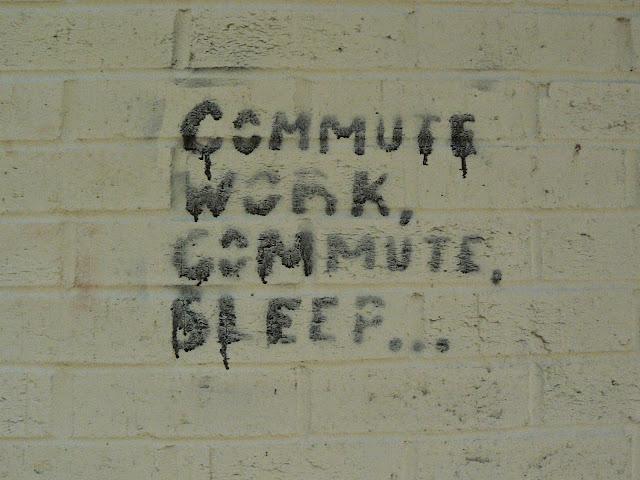 Graffiti on a wall reading Commute Work, Commute Sleep....