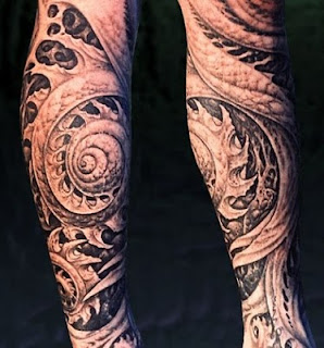 biomechanic tattoo on the leg: alien-like tentacles