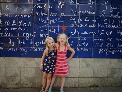 Deux soeurs complices devant le mur des je t'aime