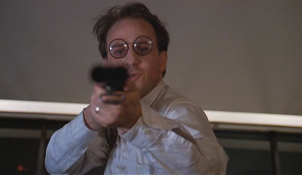 Bobcat Goldthwaite holding a gun in Scrooged 1988 movieloversreviews.blogspot.com