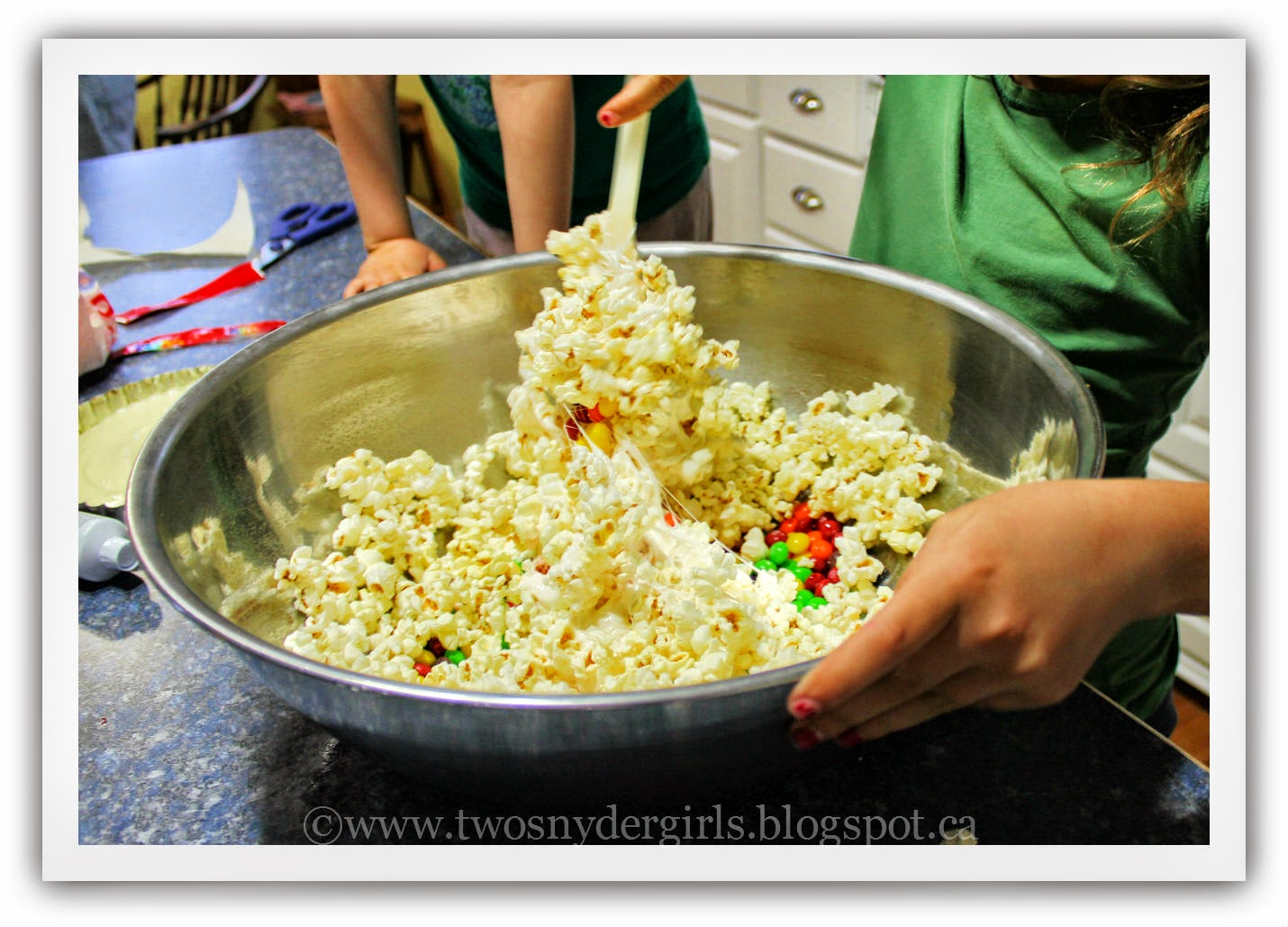 Mixing popcorn candy and melted marshmallows