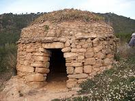 La barraca de Cal Barrab és de planta rodona, amb la porta d'arc apuntat i llinda simple