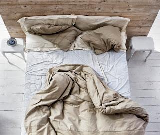 Un lit avec des draps froissés