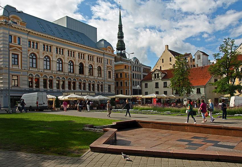 Vista sobre a praça, com zona relvada e calçada em primeiro plano e ao fundo, toldos e pessoas em circulação. Por detrás, prédios de bela arquitectura e uma torre contra o céu nublado