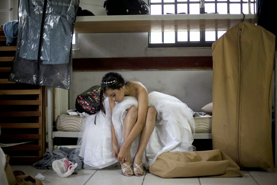 "A teenage girl from the Santa Marta ""favela"" slum puts on a pair of high heels for a group debutante ball organized by the Pacifying Police Unit from her neighborhood in Rio de Janeiro, Brazil, Friday, Aug. 29, 2014."