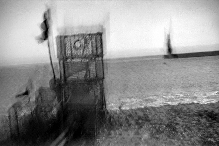 Imagem a preto e branco, muito turva, resultado de movimento da câmara durante a mesma exposição. Perceptível, uma armadilha para a pesca em primeiro plano, a zona de rebentação das ondas e um quebra-mar ao longe. Linha do horizonte muito inclinada.