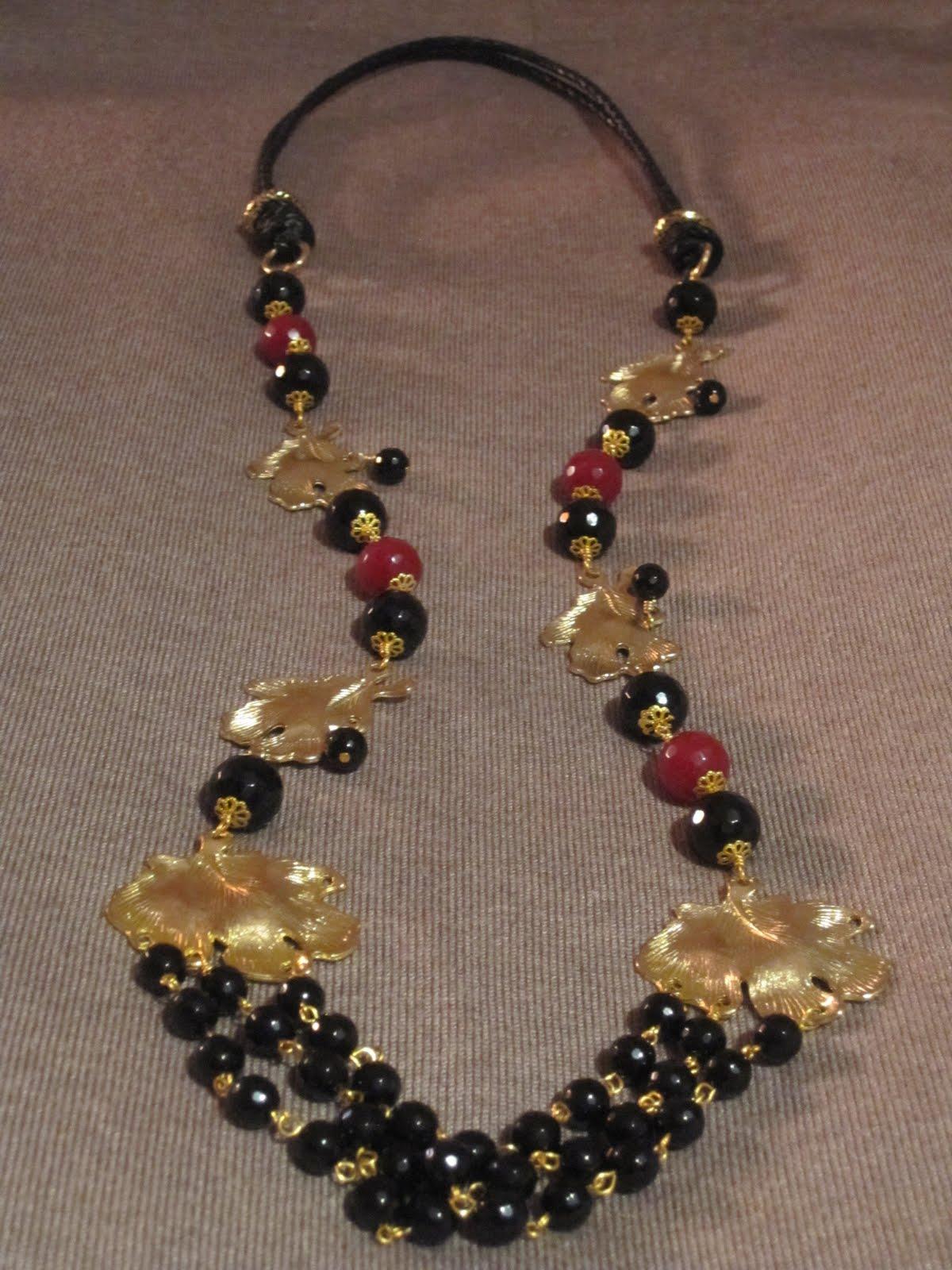 Collar largo en dorado con entrepiezas doradas en formas de hojas, bolas facetadas con casquillas (onix,negras y jades,granates), bolas de onix facetado más