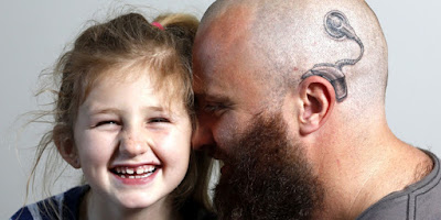 little girl facing forward, man facing girl with shaved head and tattoo of choclear implant