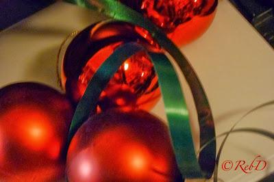 Fyra röda julgranskulor och grönt snöre på vitt papper. foto: Reb Dutius